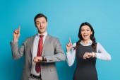dva usměvaví podnikatelé zobrazující náznaky nápadů při pohledu na kameru na modrém pozadí