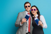 Photo happy businessman and businesswoman in sunglasses holding passports and air tickets on blue background