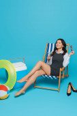 Photo happy businesswoman sitting with closed eyes in deck chair with glass of cocktail near portable fridge, inflatable ring and ball on blue background