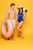 happy woman in swimsuit holding passports and air tickets while touching shoulder of shirtless man with inflatable ring on yellow background