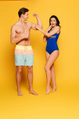 Photo suprised woman in swimsuit touching biceps of handsome shirtless man on yellow background