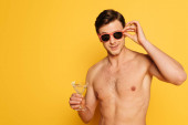 Photo shirtless man touching sunglasses while holding glass of cocktail on yellow background