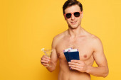 Photo shirtless man in sunglasses holding glass of cocktail, passports and air tickets on yellow background