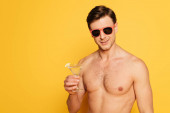 Photo shirtless man in sunglasses holding glass of cocktail on yellow background