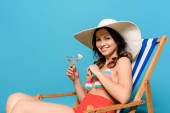 boldog nő mosolyog a kamera, miközben ül fedélzeti szék és kezében üveg koktél a kék háttér