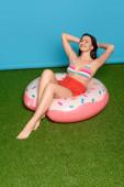 boldog, vonzó nő ül felfújható gyűrű napozás közben csukott szemmel kék háttér