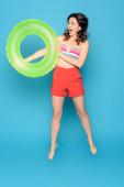 vzrušená žena skákání s nafukovací kroužek na modrém pozadí