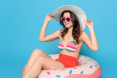Fotografie smiling, stylish woman in sunglasses touching sun hat while sitting on swim ring on blue background