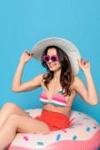 šťastná, stylová žena v slunečních brýlích dotýkající se slunečního klobouku při sezení na plaveckém prstenu na modrém pozadí
