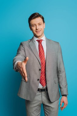 Smiling businessman showing greeting gesture with outstretched hand while looking at camera on blue background stock vector
