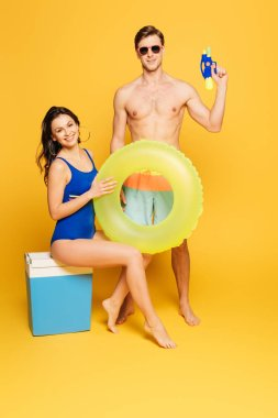 Cheerful woman sitting on portable fridge with swim ring near shirtless man holding water gun and on yellow background stock vector