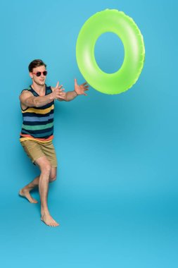 Young man in striped singlet and shorts throwing inflatable ring on blue background stock vector