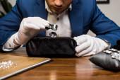Oříznutý pohled znalce šperků zkoumající drahokam v blízkosti náušnic na šperkovém polštáři na stole