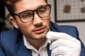 Selektivní zaměření posuzovatele šperků v rukavicích a brýlích s kroužkem s drahokamem v dílně