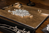Selective focus of gemstones, magnifying glasses and jewelry on board on wooden table