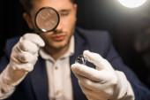 Selektivní zaměření klenotnictví odhadce zkoumání drahokam s lupou na černém pozadí