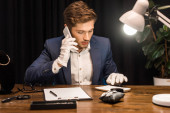 Jewelry appraiser talking on smartphone and using calculator near jewelry on table