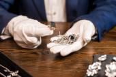 Oříznutý pohled na klenotnictví odhadce držení prsten a šperky u stolu izolované na černé