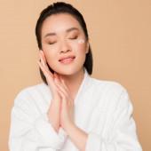 erfreut schöne asiatische Frau im Bademantel mit Gesichtscreme auf der Wange und geschlossenen Augen auf beigem Hintergrund