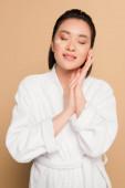potěšen krásný asijské žena v županu s obličejem krém na tváři a zavřené oči na béžové pozadí