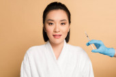 beautiful asian woman in bathrobe near cosmetologist hand with syringe for beauty injection on beige background