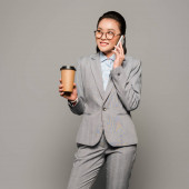 Photo smiling young businesswoman in eyeglasses holding paper cup and talking on smartphone on grey background