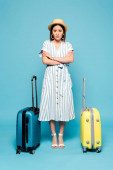 smutná brunetka asijské dívka v pruhované šaty a slamák klobouk s cestovní tašky na modrém pozadí