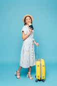 usmívající se brunetka asijské dívka v pruhovaných šatech a slamák klobouk s cestovní taškou a pas s letenkou na modrém pozadí