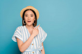surprised brunette asian girl in striped dress and straw hat pointing with finger aside on blue background