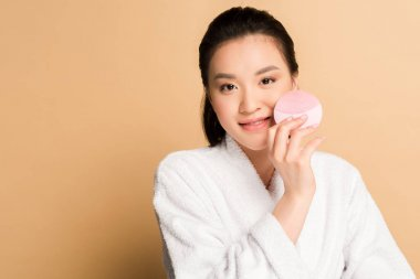 Beautiful asian woman in bathrobe using facial cleansing brush on beige background stock vector
