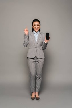 Excited young businesswoman in eyeglasses holding smartphone and showing idea gesture on grey background stock vector