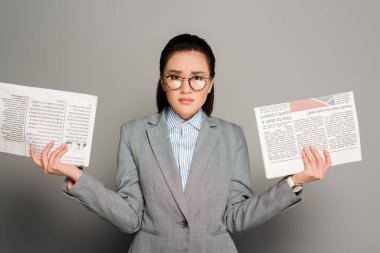 Sad young businesswoman in eyeglasses holding newspapers on grey background stock vector