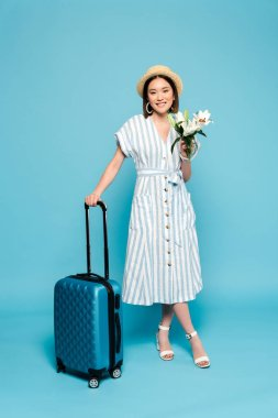 Smiling brunette asian girl in striped dress and straw hat with travel bag and bouquet of lilies on blue background stock vector