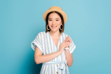 Smiling brunette asian girl in striped dress and straw hat on blue background stock vector