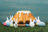 Fotografie Easter bread with colorful eggs and decorative bunnies on grass