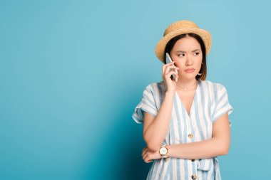 Sad brunette asian girl in striped dress and straw hat taking on smartphone on blue background stock vector