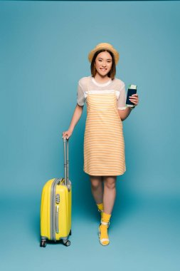 Smiling asian girl in striped yellow dress and straw hat holding passport and suitcase on blue background stock vector