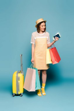 Smiling asian girl in striped yellow dress and straw hat with shopping bags, passport and suitcase on blue background stock vector