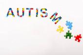 Horní pohled na autismus puzzle nápis na bílém pozadí