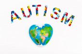 Draufsicht auf Autismus-Puzzle Schriftzug und Globus isoliert auf Weiß