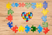 Top view of decorative heart with pieces of puzzle on wooden background, autism concept