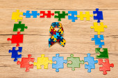 High angle view of awareness ribbon with colorful pieces of puzzle on wooden background, autism concept