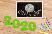 Fényképek Felülnézet tábla földnapi betűkkel, 2020 számjegyek és darabok kréta fa háttér