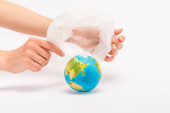 Partial view of woman holding plastic bag above globe on white, global warming concept