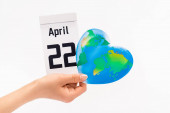 Fotografie Cropped view of woman holding calendar with 22 april inscription and globe isolated on white, earth day concept