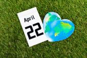 Top nézet naptár 22 Április felirat és földgömb zöld háttér, föld nap koncepció