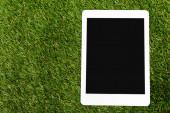 Fényképek Top view digitális táblagép zöld háttér, föld nap koncepció