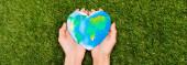 Fotografie Oříznutý pohled na zeměkouli v ženských rukách na zeleném, zemský koncept