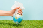 Cropped view of woman holding plastic bag with globe on green and blue, global warming concept