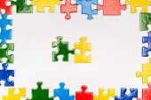 Top view of frame with multicolored pieces of puzzle on white background, autism concept